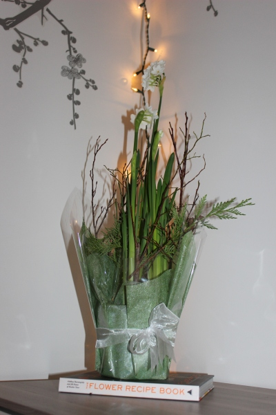 "A beautiful arrangement of paperwhites I picked up from the florist atop my ""Flower Recipe Book"". Christmas may be over but I can't resist leaving up some white lights."