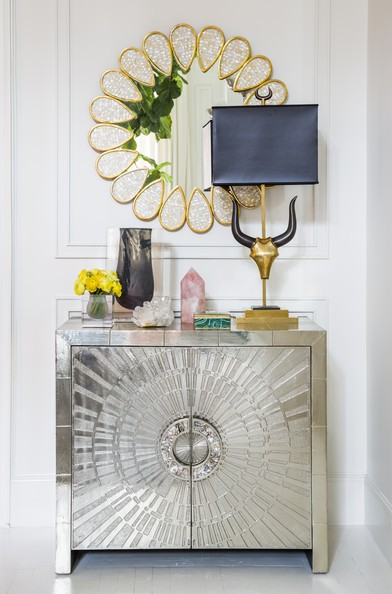 The mirror relates well both to the silver console and the bronze lamp.